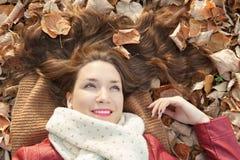 Retrato que miente en las hojas, visión superior de la mujer joven Foto de archivo libre de regalías