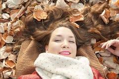 Retrato que miente en las hojas, visión superior de la mujer joven Imagen de archivo