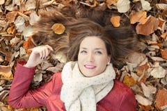 Retrato que miente en las hojas, visión superior de la mujer joven Foto de archivo