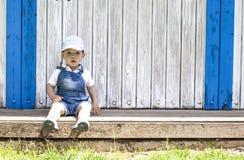 Retrato que se sienta del muchacho de 2 años en la choza de madera de la playa Foto de archivo libre de regalías