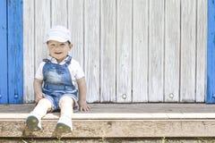 Retrato que se sienta del muchacho de 2 años en la choza de madera de la playa Fotografía de archivo
