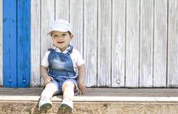 Retrato que se sienta del muchacho de 2 años en la choza de madera de la playa Fotografía de archivo libre de regalías