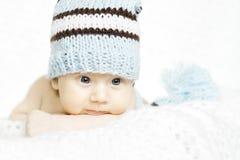 Retrato recién nacido del bebé en cierre de lana azul del sombrero para arriba imagenes de archivo