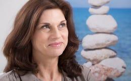 Retrato relaxado e feliz da mulher mais idosa com um veado da pedra azul fotografia de stock