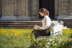 Retrato retro de uma menina sonhadora bonita que lê um livro fora Tonificação macia do vintage Foto de Stock