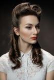 Retrato retro de una muchacha hermosa con los labios del peinado y del rojo Foto de archivo libre de regalías