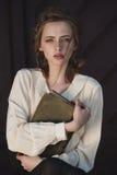 Retrato retro de una muchacha soñadora hermosa que sostiene un libro en manos al aire libre Tono suave del vintage Foto de archivo