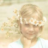 Retrato retro texturizado de la muchacha rubia bastante pequeña con una corona de margaritas Imagen de archivo