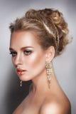 Retrato rubio de la mujer de la belleza con joyería y pendientes de oro del pelo Imagenes de archivo