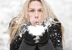 Retrato rubio de la mujer del pelo largo hermoso Ella sopla nieve a la dirección de la cámara Imagen de archivo libre de regalías