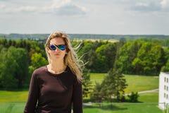 Retrato rubio de la mujer joven de la belleza con las gafas de sol y paisaje blured en fondo fotografía de archivo libre de regalías