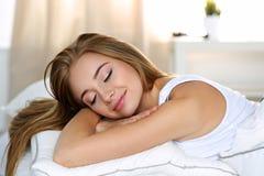 Retrato rubio hermoso joven de la mujer que miente en cama foto de archivo