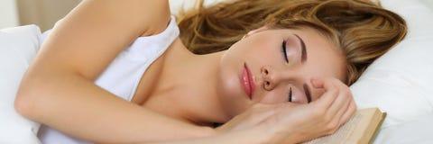 Retrato rubio hermoso joven de la mujer que miente en la cama que duerme en b fotografía de archivo