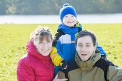 Retrato sazonal exterior da família de três povos alegres no parque imagem de stock royalty free