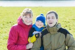 Retrato sazonal exterior da família de três povos de sorriso no parque fotografia de stock