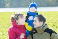 Retrato sazonal exterior da família de três povos felizes no parque fotos de stock royalty free