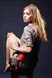 Retrato sedutor da mulher nova que senta-se na cadeira Fotos de Stock Royalty Free