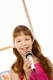 Retrato si chica joven con el micrófono Fotos de archivo libres de regalías