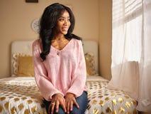 Retrato sincero de la mujer afroamericana joven que lleva la sentada rosada del suéter en cama en casa fotos de archivo libres de regalías