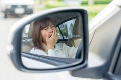 Retrato soñoliento, mujer joven cansada del primer que conduce su coche después fotos de archivo