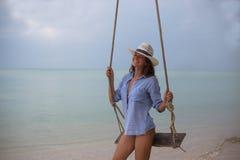 Retrato solar del verano de la moda de una manera de vida de la mujer elegante joven, sentándose en un oscilación en la playa, fa Imagen de archivo libre de regalías