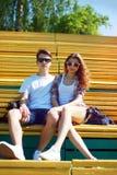 Retrato soleado de los pares despreocupados jovenes elegantes que se sientan en parque Fotos de archivo libres de regalías