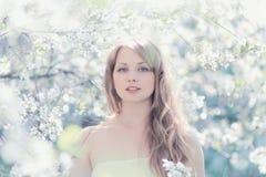 Retrato soleado de una mujer hermosa en una primavera floreciente Foto de archivo libre de regalías