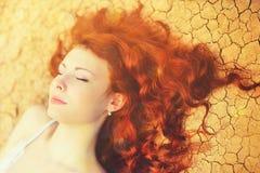 Retrato soleado de una mujer joven relajante con el pelo rojo rizado largo elegante que miente en la tierra agrietada imagen de archivo