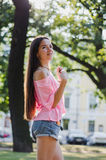 Retrato soleado del verano de la muchacha elegante del inconformista con el pelo largo en el parque, sonriendo y divirtiéndose, c Imagen de archivo