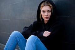 Retrato solo y triste de la muchacha en la pared negra Imagen de archivo libre de regalías