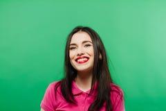Retrato sonriente atractivo de la mujer en fondo verde Foto de archivo