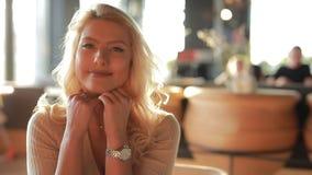 Retrato sonriente de la mujer atractiva bonita, cabeza que se inclina en las manos metrajes