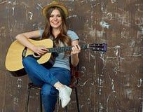 Retrato sonriente de la mujer joven con la guitarra acústica Imagen de archivo libre de regalías