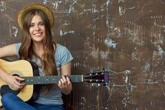 Retrato sonriente de la mujer joven con la guitarra acústica Foto de archivo libre de regalías