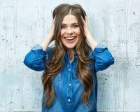 Retrato sonriente de la mujer joven contra la pared gris Fotografía de archivo