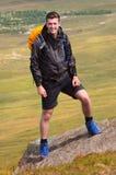 Retrato sonriente del caminante en el top de la montaña Fotografía de archivo libre de regalías