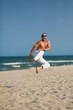 Retrato sonriente del hombre que se sienta en la playa Imagen de archivo