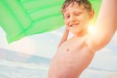 Retrato sonriente del mar del muchacho con el colchón verde de la natación del aire Imágenes de archivo libres de regalías