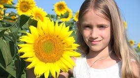 Retrato sonriente del niño en el campo del girasol, niña feliz que juega 4K al aire libre