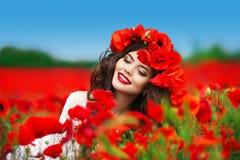 Retrato sonriente feliz hermoso de la mujer con las flores rojas en la cabeza Foto de archivo