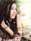 Retrato sonriente tranquilo de la muchacha con los dreadlocks, descansando sobre la hierba seca en parque Fotos de archivo