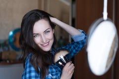 Retrato suave de una mujer joven con un maquillaje natural ligero en el espejo redondo del maquillaje con los cepillos del cosmét Fotos de archivo