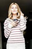 Retrato suave del adolescente que bebe el café caliente en casa, estilo del instagram entonado Imagenes de archivo