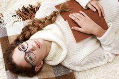 Retrato suave del libro de lectura del adolescente en casa Fotos de archivo