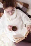 Retrato suave del libro de lectura del adolescente en casa Imagenes de archivo