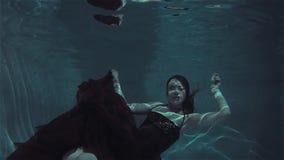Retrato subacu?tico m?stico de una mujer joven hermosa en un vestido rojo almacen de video