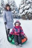 Retrato superior da mãe e da jovem criança com tubulação da neve Fotografia de Stock Royalty Free