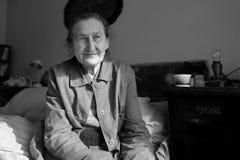 Retrato superior da mulher dos anos de idade 80 positivos bonitos Imagem preto e branco da mulher preocupada idosa que senta-se e Fotografia de Stock Royalty Free