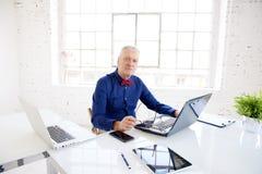 Retrato superior do homem de negócios ao trabalhar em portáteis no escritório imagem de stock