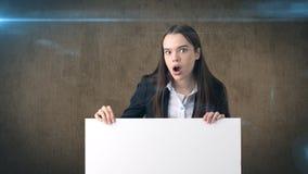 Retrato surpreendido da mulher de negócio com a placa branca vazia no marrom isolada Modelo fêmea com cabelo longo Imagens de Stock